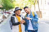 Two Male Friends Walking Together In The Street While Using Cell Phone. poster