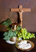 Holy communion image showing a golden chalice with grapes and bread wafers