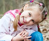 stock photo of cute little girl  - Cute little girl  on the wood in spring day - JPG