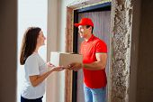 Woman Receiving Parcel From Delivery Service Courier Indoors. Woman And Courier During Order Transfe poster