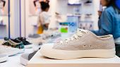 White Sneakers On The Display Table In The Fashion Shoes Store, Close-up With Blurred Background Of  poster
