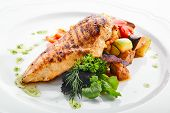 Macro shot of grilled chicken fillet with side dish of baked vegetables on white restaurant plate is poster