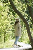 Girl On A Walk In The Park. A Slender Girl In A Straw Hat Walks In The Park In Sunny Weather. A Girl poster