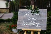 Wooden Board With The Inscription Welcome To Our Wedding Decorated With Green Branches. Wedding Cere poster