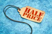 half price sign - a paper price tag with a twine against blue textured paper, shopping marketing con poster