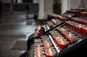 Candles In The Church. Votive Prayer Candles Inside A Catholic Church On A Candle Rack poster