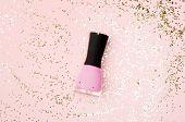 Nail Polish Bottle On Golden Glittering Background. Pink Fingernail Varnish On Nude Backdrop With Sh poster