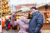 travel, tourism, holidays and people concept - happy senior couple hugging at christmas market on to poster