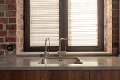 Stainless Kitchen Sink With Modern Faucets Against Window With Shutters In Red Brick Wall poster