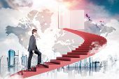 Young Man In Glasses Climbing Staircase In Sky Leading To Large Book. Cityscape Below Him. World Map poster