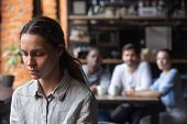 Upset Mixed Race Woman Suffering From Bullying, Sitting Alone In Cafe poster