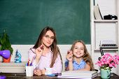 Little Girl And Woman Sit At Desk. School Education. Studying Together. Help With Homework. Homework poster