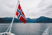 Norwegian Flag Hanging On The Railing Of The Ship And Waving Above The Water. Norvegian Fjord With A poster