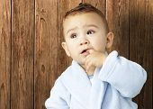 portrait of an adorable infant with his finger in his mouth wearing a bathrobe against a wooden background