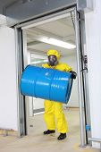 Worker in protective uniform,mask,gloves and boots lifting barrel of toxic substance