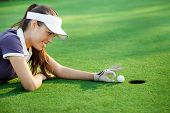 female golfer flick the golf ball into the hole