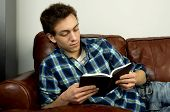 Young Man On Couch Reading Book