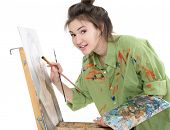 attractive teen girl painter drawing portrait with oil paints, professional painter at work over whi