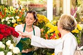 Senior customer buying red roses flower shop florist women working