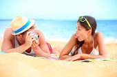 Young couple having fun on beach with vintage retro camera. Funky young interracial couple playful o