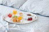 image of pillowcase  - Tray with tasty breakfast on a bed with gray bed linen.