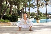 pic of kundalini  - Photo of a middle aged lady doing a yoga pose in a beautiful hotel garden - JPG