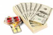 Pílulas e dinheiro isolado no branco