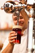 stock photo of drawing beer  - Detail of a bartender drawing a beer - JPG