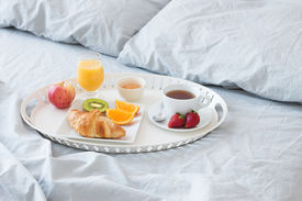 pic of pillowcase  - Tray with tasty breakfast on a bed with gray bed linen. ** Note: Shallow depth of field - JPG