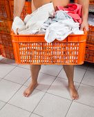 Low section of semi nude man carrying clothes basket in laundry