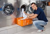 stock photo of laundromat  - Portrait of young man putting clothes in washing machine at laundromat - JPG