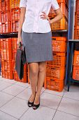 Low section of young businesswoman standing with hand on hip and crates in background at laundromat