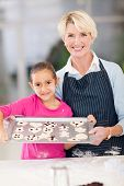 grandmother and granddaughter holding tray of homemade cookies to be baked