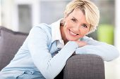 stock photo of couch  - pretty senior woman relaxing on a couch at home - JPG
