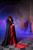 Beautiful gothic victorian woman in red standing in a smokey dark medieval castle