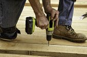 Carpenter's hands using cordless power drill