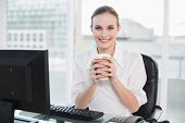 Businesswoman holding disposable cup smiling at camera in her office