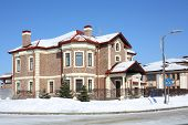 stock photo of peace-pipe  - Brown cottage with red roof and drain at frosty and sunny winter day - JPG