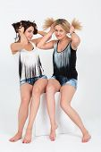 Girls having fun with hair sitting on a white cube in studio