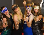 Happy friends wearing masks showing champagne glasses and posing