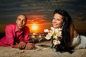 Portrait of bride and groom with golden fish making wish at sunset on sea