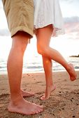 Love - romantic couple dating on beach kissing and embracing. Happiness and romance travel concept w