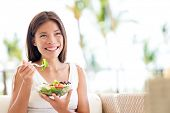 Healthy lifestyle woman eating salad smiling happy outdoors on beautiful day. Young female eating healthy food outside in summer dress laughing and relaxing in sofa. Pretty multiracial model.