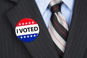stock photo of lapel  - A male voter in his business suit wearing a vote pin on his lapel - JPG