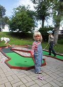 image of miniature golf  - Three hillybilly looking kids playing miniature golf - JPG