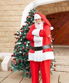 Portrait of confident Santa Claus standing arms crossed outside house