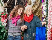 Happy mother and daughter shopping for Christmas ornaments in store