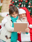 Santa Claus using digital tablet with boy in front of Christmas tree