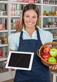 Portrait of happy saleswoman holding digital tablet and fruits basket in grocery store