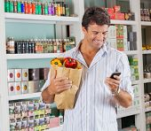 stock photo of supermarket  - Happy male customer with grocery paper bag using mobile phone in supermarket - JPG